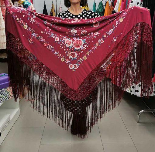 Mantón de Manila de color burdeos con bordados florales, flecado a mano y es muy apropiado para el baile por su tamaño, pesa y buen precio. Medidas: 140 cm. X 140 Cm. (+18 cm. el enrejado).
