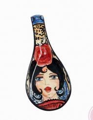 Portacucharas de cerámica flamenca de la artista Catalina Alcaide. Largo: 29 cm y ancho: 10,5 cm. Catalina Alcaide inició su andadura en la decoración de piezas en 1978, trabajando para algunos de los principales talleres de cerámica deLa Rambla. Su primera exposición de trabajos tuvo lugar en 1982, en el Palacio de La Merced de Córdoba, con tan solo 18 años. Colaboró en el taller del ilustre escultor, pintor y ceramistaAlfonso Ariza, el cual destacó sus méritos otorgándole la medalla de plata en 1982 por su destacada labor como decoradora de cerámica.